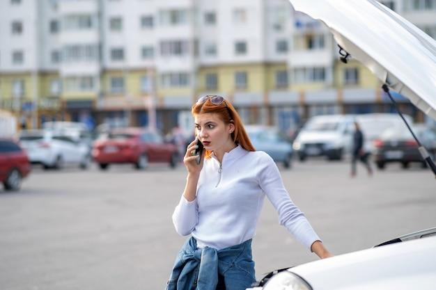 Mujer joven de pie cerca de un coche roto con capucha reventada hablando por su teléfono móvil mientras espera ayuda.