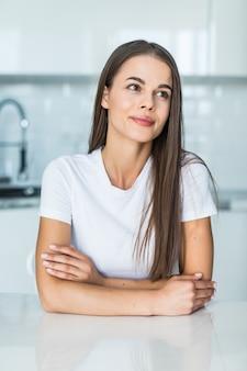 Mujer joven de pie cerca del escritorio en la cocina.