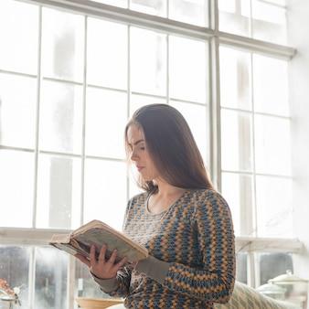 Mujer joven de pie cerca de la ventana leyendo un libro viejo