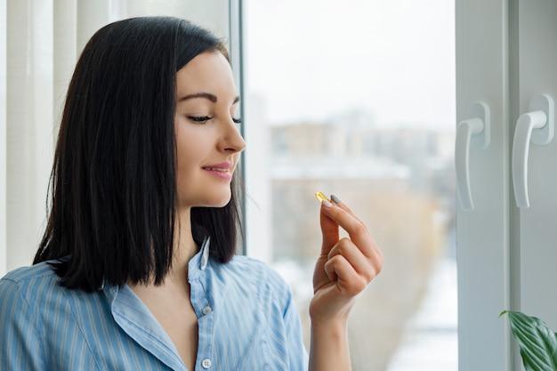 Mujer joven de pie cerca de la ventana tomando vitamina