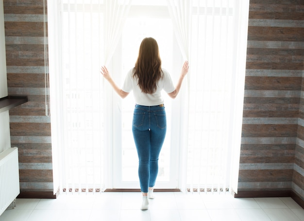 Mujer joven de pie en la cocina durante la cuarentena. vista posterior de la persona femenina mirar ventana y tomarse de las manos en las cortinas. autoaislamiento en casa. hermosa luz blanca del día.