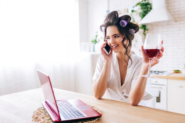 Mujer joven de pie en la cocina y hablando por teléfono. sosteniendo copa de vino tinto en la mano. ama de llaves con rulos en el pelo. ama de casa descuidada vida.