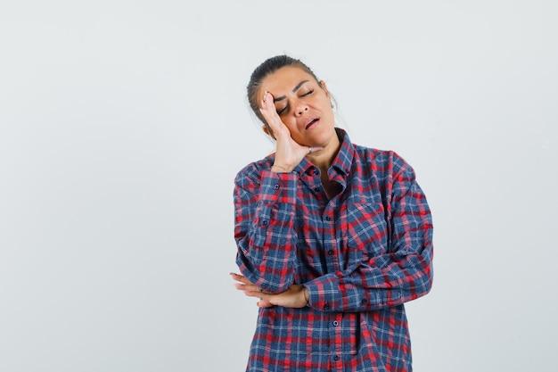 Mujer joven de pie como tratando de dormir con camisa a cuadros y con sueño. vista frontal.