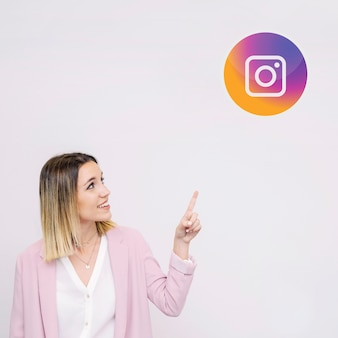 Mujer joven de pie contra el fondo blanco apuntando al logo de instagram