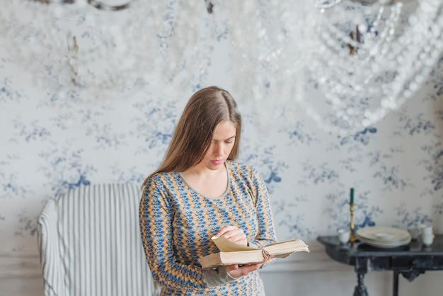 Mujer joven de pie contra el libro de lectura de fondo de pantalla