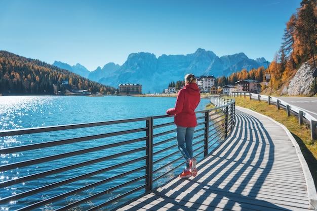 Mujer joven de pie en la costa del lago misurina al amanecer en otoño