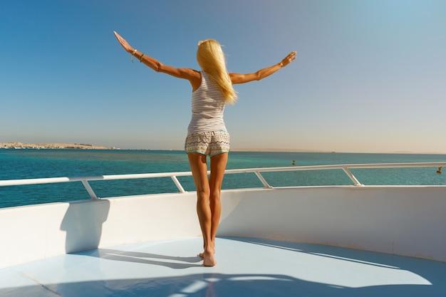 Mujer joven de pie en la cubierta de un barco en mar abierto en un día soleado de verano