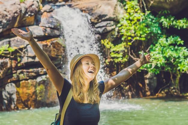 Mujer joven de pie delante de la cascada con las manos levantadas