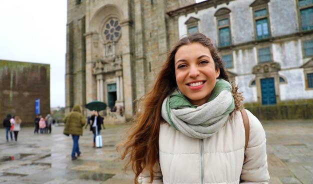 Mujer joven de pie delante de la catedral de oporto