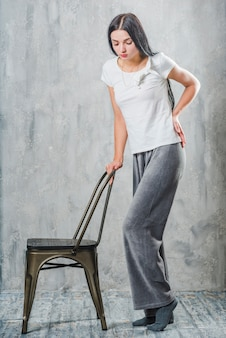 Mujer joven de pie detrás de la silla que tiene dolor de espalda