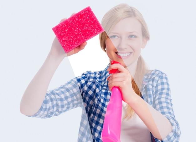 Mujer joven de pie detrás de la ventana y lavándolo