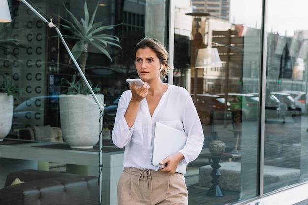 Mujer joven de pie en la entrada del edificio de oficinas usando grabadora de comandos de voz