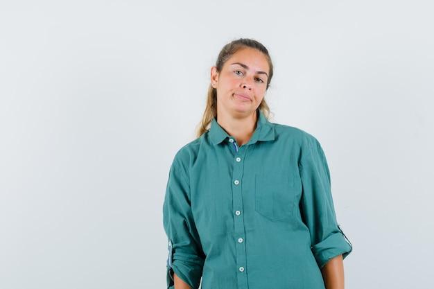 Mujer joven de pie con la espalda recta y posando al frente en blusa verde y luciendo lindo