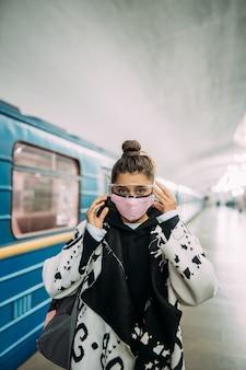 Mujer joven de pie en la estación de máscara protectora médica