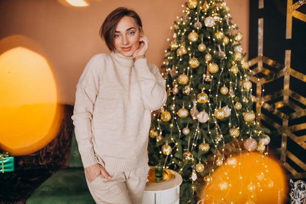 Mujer joven de pie junto al árbol de navidad