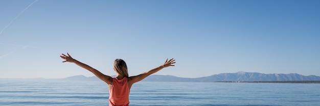 Mujer joven de pie junto al mar de la mañana saludando el nuevo día