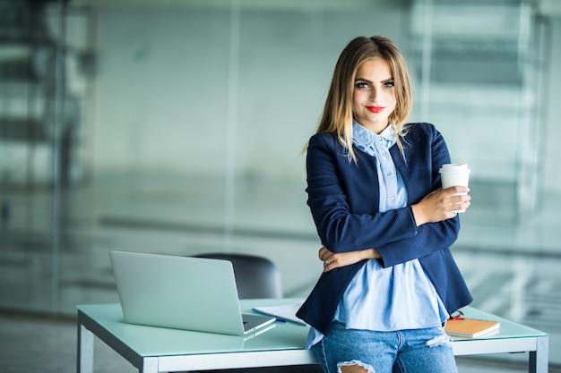 Mujer joven de pie junto a la mesa con portátil con carpeta y taza de café. lugar de trabajo. mujer de negocios.