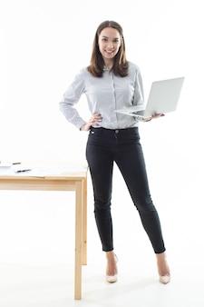 Mujer joven está de pie junto a la mesa y trabaja en una computadora