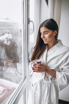 Mujer joven de pie junto a la ventana tomando café caliente