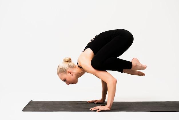 Mujer joven de pie en las manos en la clase de yoga