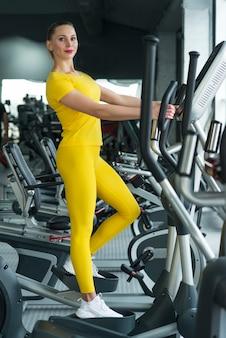 Mujer joven de pie en la máquina elíptica en el gimnasio