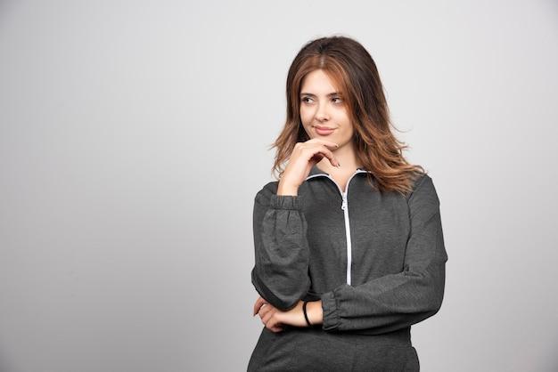 Mujer joven de pie y mirando a otro lado sobre una pared gris.