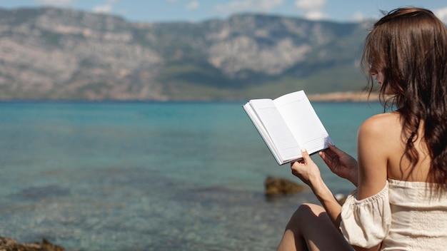 Mujer joven de pie en la orilla del mar con un libro