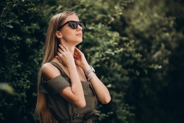Mujer joven de pie en el parque en el fondo verde arbusto