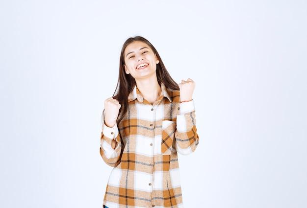 Mujer joven de pie y posando en la pared blanca.