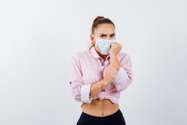 Mujer joven de pie en pose asustada en camisa, pantalón, máscara médica y mirando asustado, vista frontal.