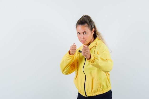 Mujer joven de pie en pose de boxeador en chaqueta de bombardero amarillo y pantalón negro y mirando lindo