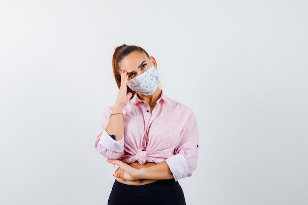 Mujer joven de pie en pose de pensamiento en camisa, pantalón, máscara médica y mirando pensativo. vista frontal.