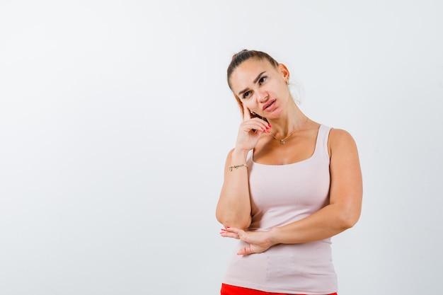 Mujer joven de pie en pose de pensamiento en camiseta y mirando vacilante. vista frontal.