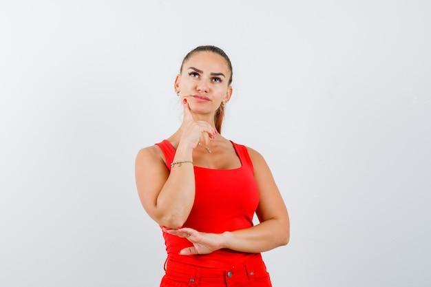Mujer joven de pie en pose de pensamiento en camiseta roja, pantalones y mirando pensativo. vista frontal.