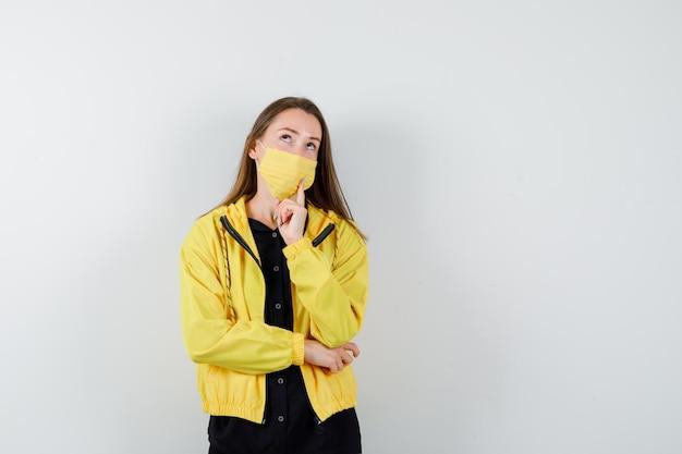 Mujer joven de pie en pose de pensamiento y poniendo el dedo índice en la barbilla