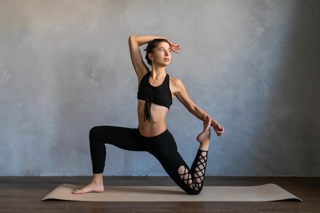 Mujer joven de pie en una posición de ejercicio de yoga. equilibrio de niña, práctica de ejercicios de estiramiento en la clase de yoga.
