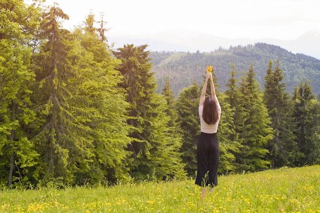 Mujer joven de pie con un ramo de flores y manos levantadas. bosque y montañas