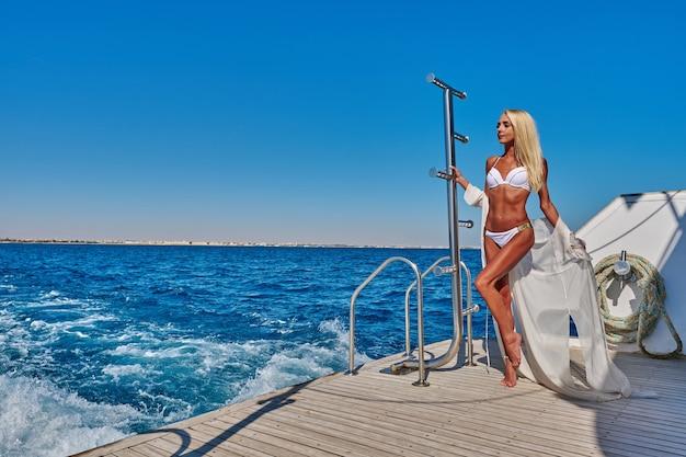 Mujer joven de pie sobre la cubierta de un barco en mar abierto en un día soleado de verano