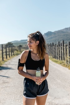 Mujer joven de pie y sosteniendo la botella con bebida energética