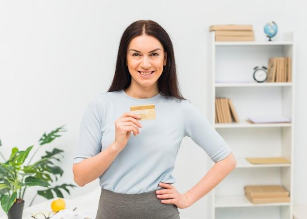 Mujer joven de pie con tarjeta de crédito en la oficina