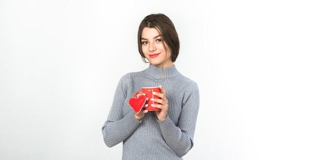 Mujer joven de pie con taza y corazón pequeño
