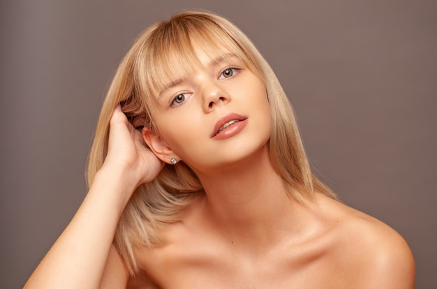 Mujer joven con piel sana fresca y pelos tocando su rostro.