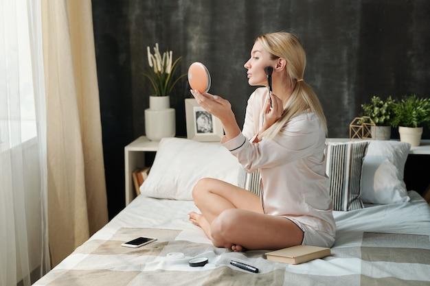 Mujer joven con las piernas cruzadas en pijama sentado en la cama mientras se aplica polvo en la cara durante la preparación para el trabajo