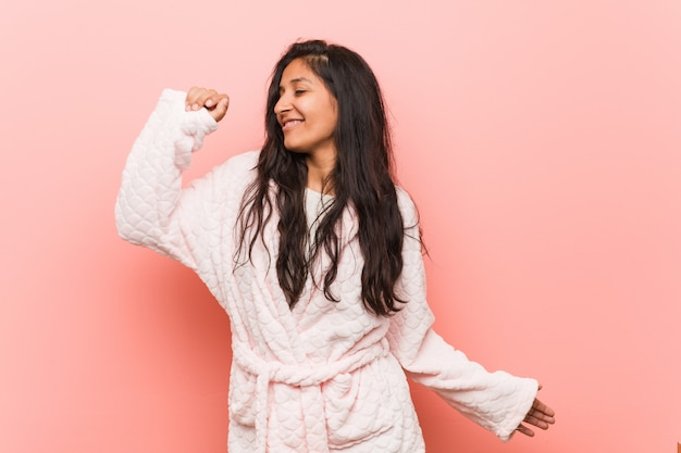 Mujer joven con pijama bailando y divirtiéndose.