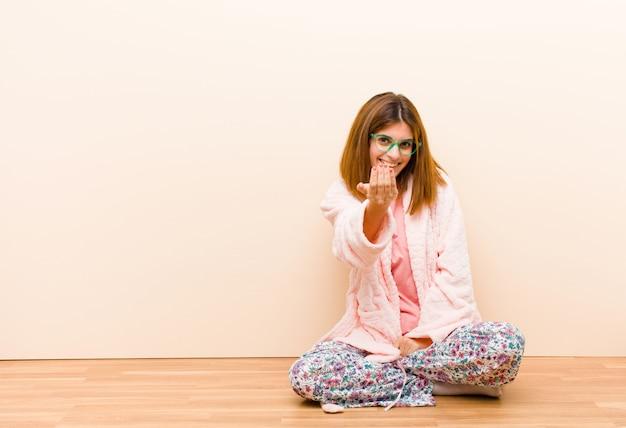 Mujer joven con pijama sentada en casa sintiéndose feliz, exitosa y segura, enfrentando un desafío y diciendo ¡adelante! o darle la bienvenida