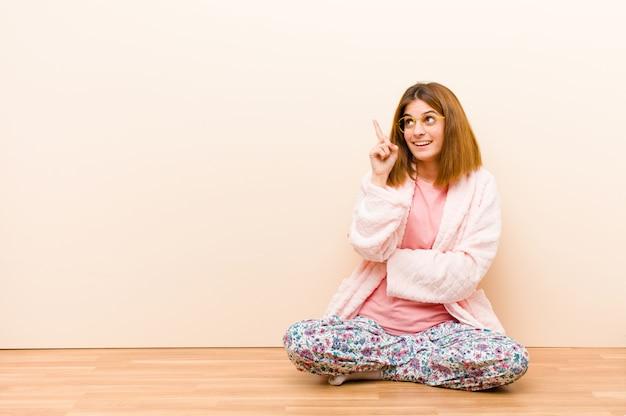 Mujer joven con pijama sentada en casa sonriendo alegremente y mirando hacia los lados, preguntándose, pensando o teniendo una idea