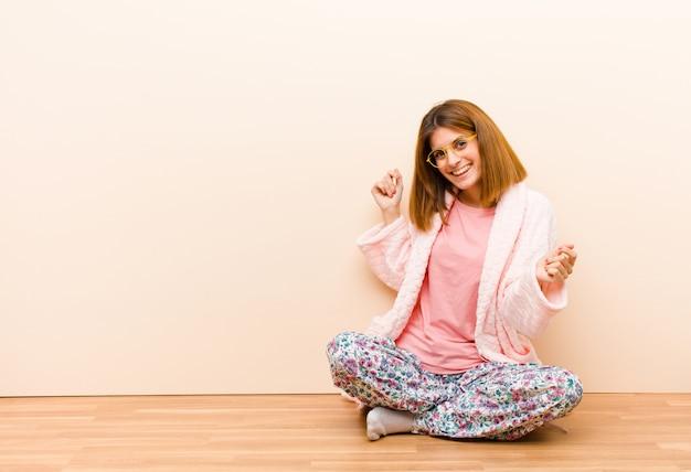 Mujer joven con pijama sentada en casa sonriendo, sintiéndose despreocupada, relajada y feliz, bailando y escuchando música, divirtiéndose en una fiesta