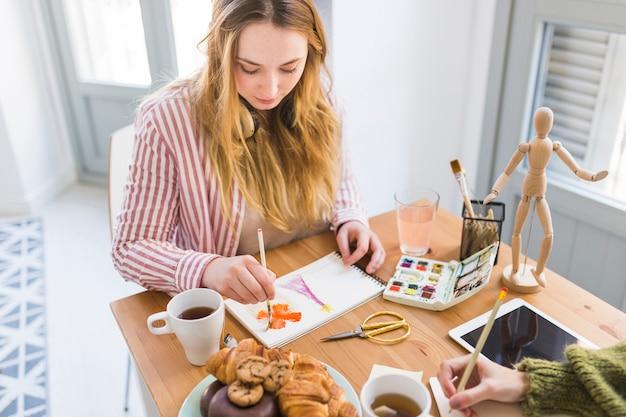 Mujer joven pintando en cuaderno de bocetos