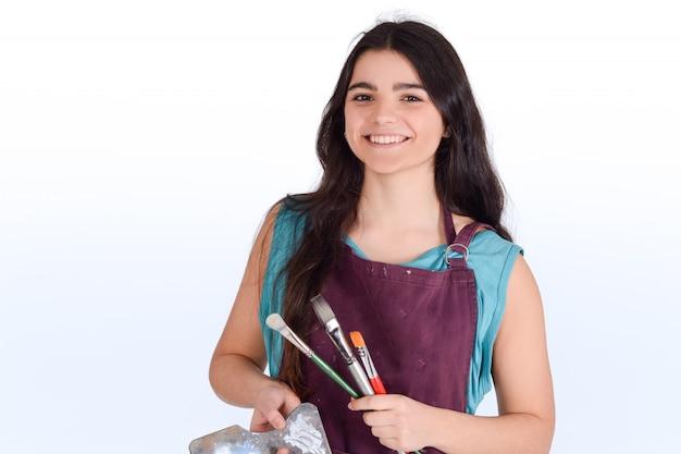 Mujer joven pintando con pincel.