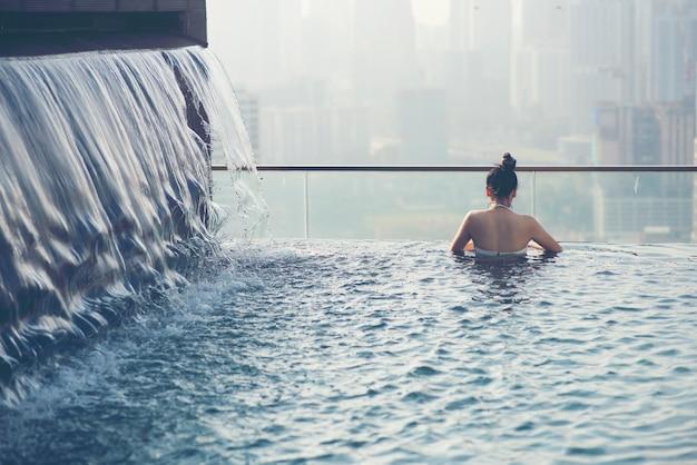Mujer joven en piscina al aire libre con vista a la ciudad por la noche